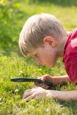 m8, boy looks through magnifying glass in garden, Bavaria, Germany